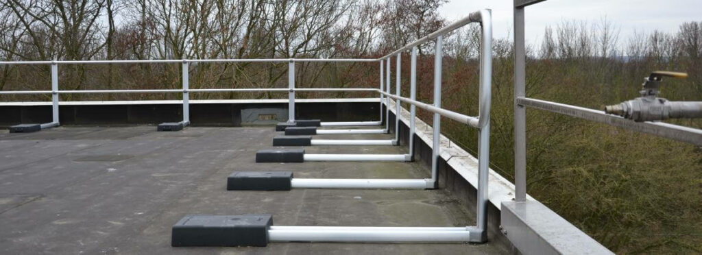Freestanding guardrails installed on a roof where the parapet is not high enough to provide safety